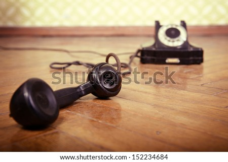 vintage old telephone, black retro phone is on the floor of used parquet, toned - stock photo