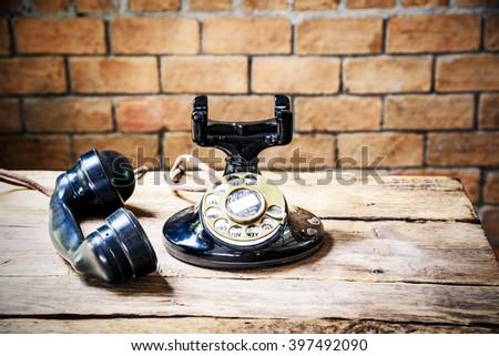 Vintage old telephone on wood table, vintage filter - stock photo
