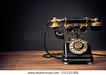 Vintage old telephone with binoculars conceptual still life - stock photo