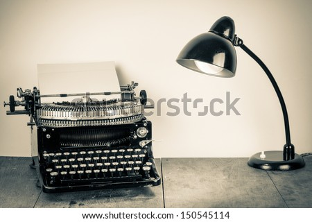 Vintage old typewriter, and lighting retro desk lamp on wood table - stock photo