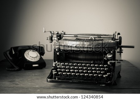 Vintage old typewriter, phone on table desaturated photo - stock photo