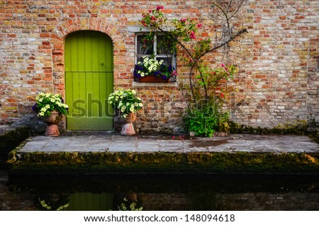 Vintage old wall with greed door and flowers, Bruges, Belgium - stock photo