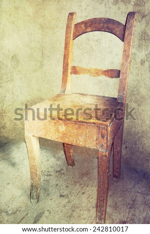 Vintage old wooden chair in grungy interior. Loneliness, estrangement, alienation concept.
