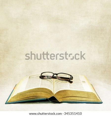 Vintage open book and classic eyeglasses - stock photo