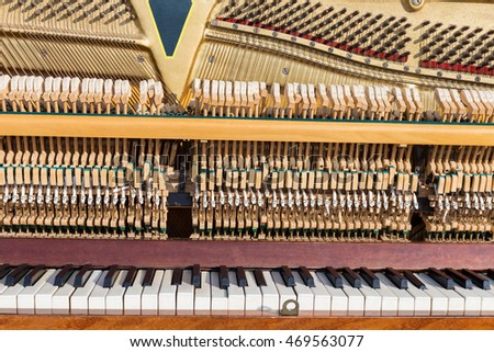 Vintage open piano with strings and hammers close-up