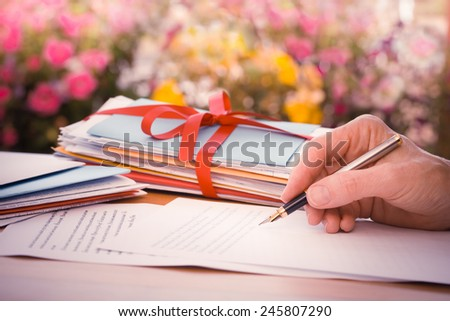 Vintage or retro style Hand with pen writing a letter by pink and yellow flowers - stock photo