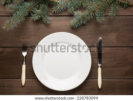 Vintage or rustic christmas table setting from above. Elegant empty white plate. - stock photo
