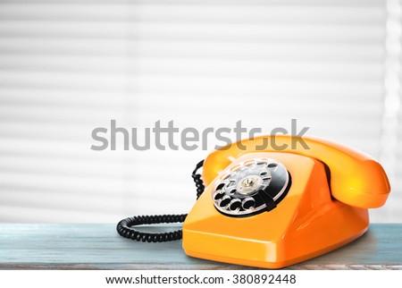 Vintage Orange phone on a table - stock photo