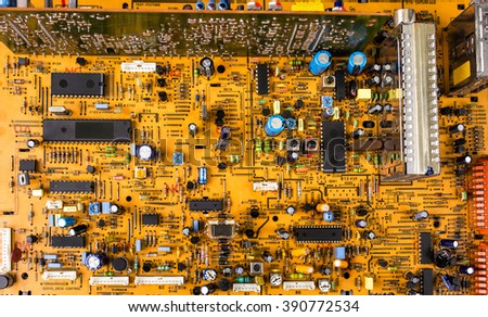 Vintage orange printed circuit board PCB with many electrical components - stock photo