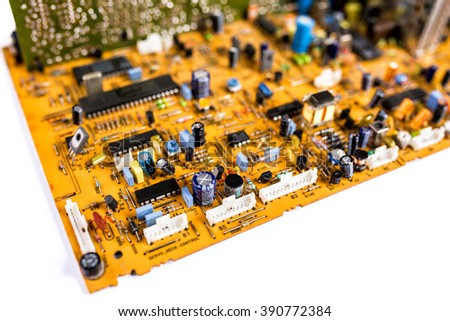 Vintage orange printed circuit board PCB with many electrical components on a white background - stock photo