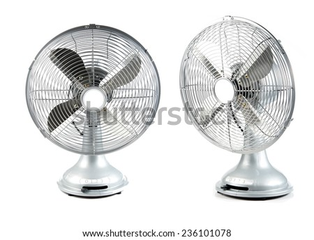 Vintage oscillating household fan, brushed silver with wire cage, four blades - stock photo