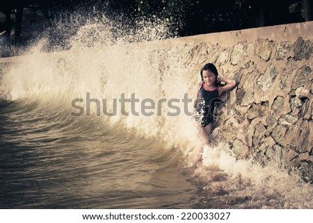 Vintage outdoor portrait of Young beautiful girl in white top in sea water splashing.