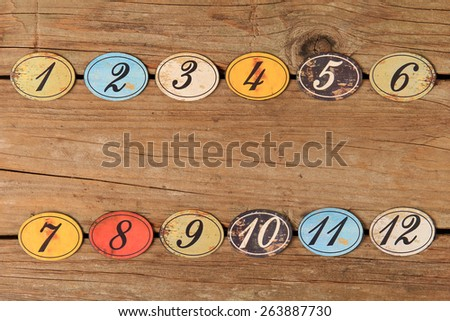 Vintage oval shaped wooden number buttons on a weather wooden table.  - stock photo