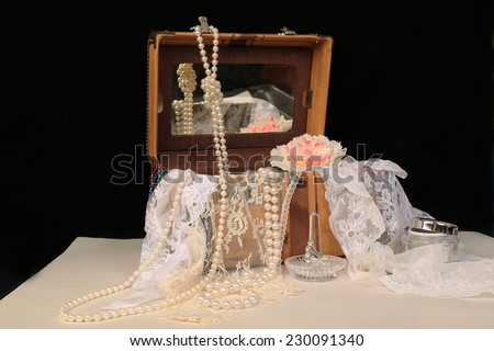 Vintage overnight case decorated with Jewelry and lace and fashion accessories in high contrast white table with black background.  Horizontal with copy space. - stock photo