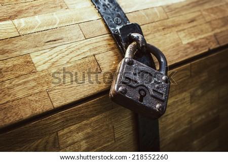 vintage padlock on wooden chest, vintage filter effect added. - stock photo