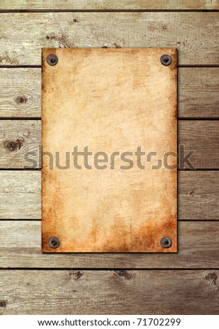 Vintage page on a wooden wall. Old paper is attached by nails.