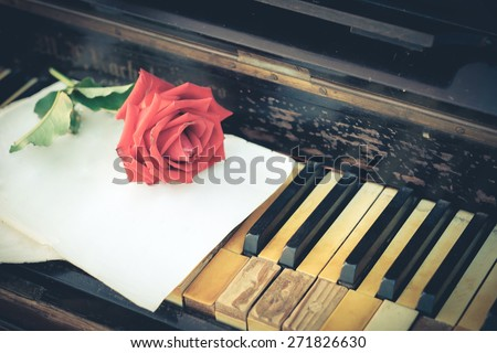 Vintage paper, roses and keys of an old piano - stock photo