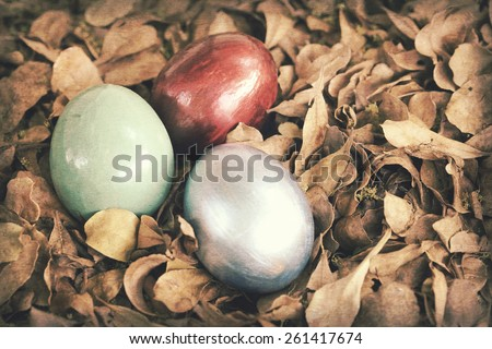 Vintage paper textures, Colorful easter eggs in pile of in weathered leaves. Spring holidays concept. - stock photo