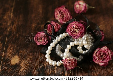 Vintage pearl with dry pink roses on a wooden background - stock photo