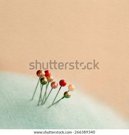 Vintage pearlized pins. Aged paper background, retro colors. Macro, extremely soft focus - stock photo