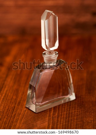 Vintage Perfume bottle decorated with pink ribbon isolated on wood background - stock photo