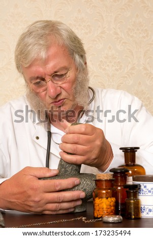 Vintage pharmacist preparing medication with mortar and pestle - stock photo