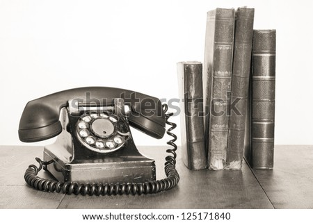 Vintage phone, old books on table sepia photo