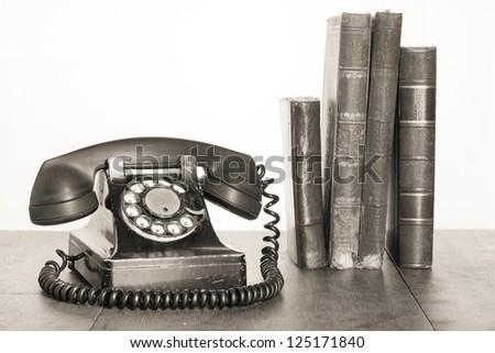 Vintage phone, old books on table sepia photo - stock photo