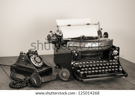 Vintage phone, old typewriter on table desaturated photo - stock photo