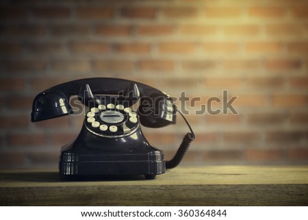 Vintage phone on the wooden floor behind a brick wall. - stock photo