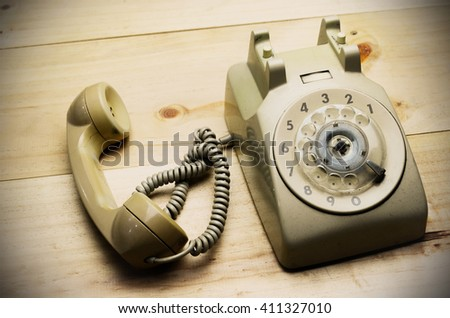 Vintage phone on wooden floor - stock photo