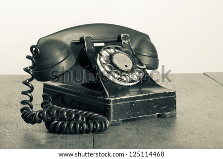Vintage phone with rotary disc on old wooden table sepia photo - stock photo