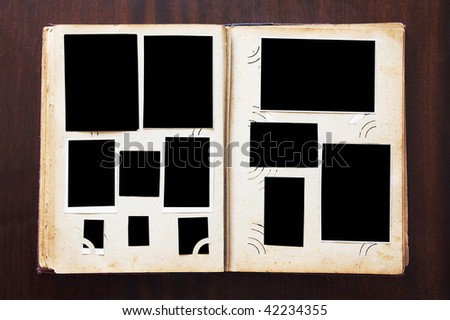 Vintage photo album with blanked photos on old wooden texture - stock photo