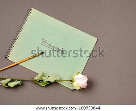 Vintage photo album with dried pink rose and antique fountain pen. - stock photo