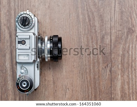 Vintage photo camera on a wooden background, top view - stock photo