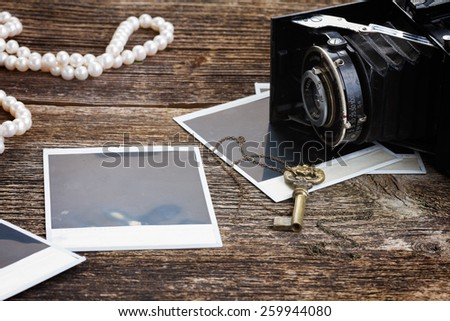 vintage  photo camera on pile of old blank instant photos with key and jewelery - stock photo