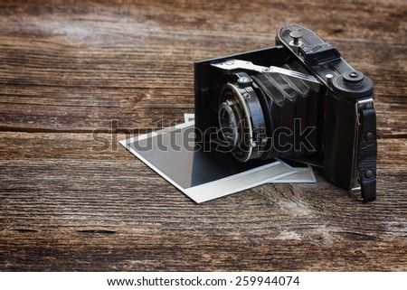 vintage  photo camera on pile of old instant photos on wooden table - stock photo