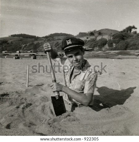Vintage photo circa 1959 of a teenage boy half buried in the sand on the beach.Organic fading scratches, and artifacts. - stock photo