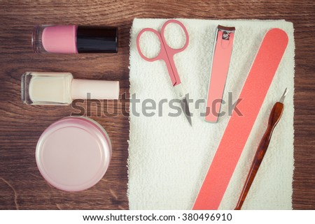 Vintage photo, Cosmetics and accessories for manicure or pedicure, nail file, nail polish and remover, scissors, nail clippers, fluffy towel, concept of nail care - stock photo