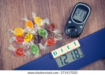 Vintage photo, Electronic bathroom scale and glucose meter with high result of measurement weight and sugar level and heap of colorful candies, diabetes, slimming and reduction eating sweets - stock photo