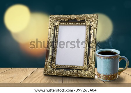 Vintage photo frame and coffee cup on wood table over abstract bokeh background