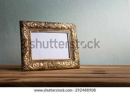 Vintage photo frame on wooden table over grunge background - stock photo