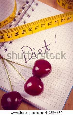 Vintage photo, Fresh cherry and tape measure with notebook for writing notes, concept of slimming, diet and healthy nutrition - stock photo