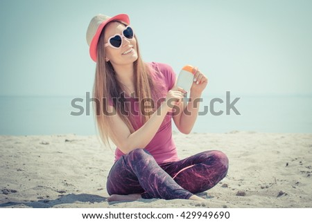 Vintage photo, Happy smiling girl wearing straw hat and sunglasses in shape of heart on seaside and holding sun lotion, sun protection on beach - stock photo
