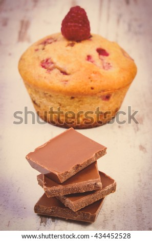 Vintage photo, Homemade fresh baked muffins with raspberries and pieces of chocolate on old rustic wooden background, delicious dessert - stock photo