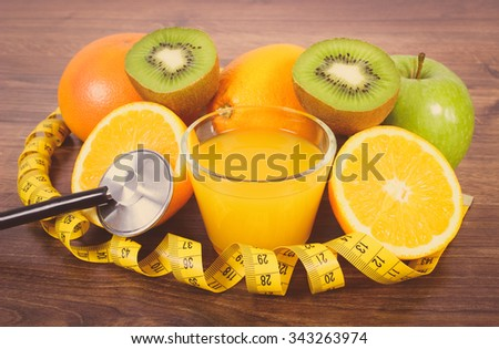 Vintage photo, Medical stethoscope and tape measure with fresh fruits and glass of juice on wooden surface plank, grapefruit orange kiwi apple, healthy lifestyles nutrition and strengthening immunity - stock photo