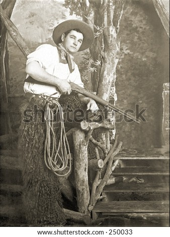 Vintage Photo of a Cowboy Holding a Rifle - stock photo