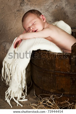 Vintage photo of a little baby of 18 days old sleeping in an antique bucket - stock photo