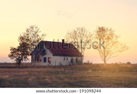 Vintage photo of abandoned house at sunrise - stock photo
