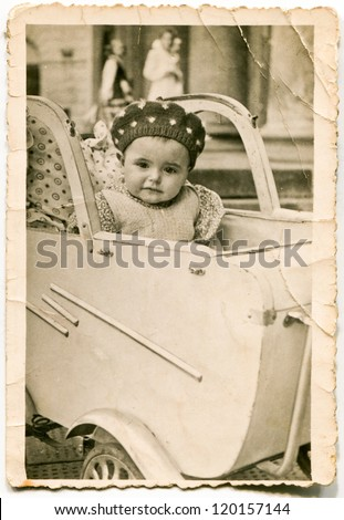 Vintage photo of baby in old fashioned pram (forties) - stock photo